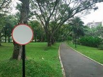 Brädet för siktscirkeltecknet och vägen för asfaltbana parkerar offentligt royaltyfri bild