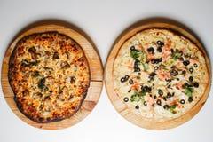 Bränd och för det normala två pizza med tomater, salami, peperoni på bästa sikt för trälantlig bakgrund Royaltyfri Bild