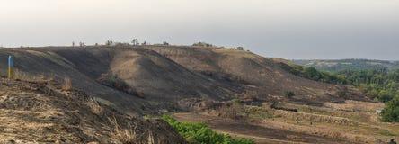 Brända kullar mot den blåa himlen i sommar Arkivfoto