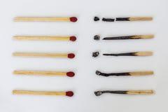 Brända matchsticks och nya matchsticks på vit bakgrund Diffe Arkivbild