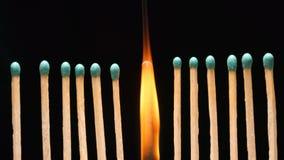 Bränna av den enkla matchsticken mellan raden av nya matchsticks Arkivfoton