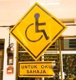 Bränna av reserverad parkering för handikapp endast tecken med malaysisk språk`-parkering för handikapp endast ` beneath Handikap Arkivfoton
