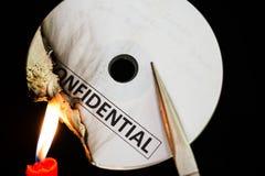 Bränna en förtrolig CD-SKIVA med stearinljuset Arkivfoton