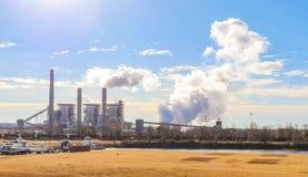 Bränna till kol den avfyrade kraftverket på en kall morgon med ånga och röka resningen - liten marina på öppning arkivfoto