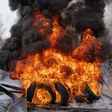 Brännande bilgummihjul, stark flamma av röd-apelsin brand, dunster för svarta moln i himmel arkivbild