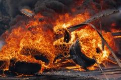 Brännande bilgummihjul, stark flamma av röd brand och moln av svarta dunster i himmel royaltyfri foto