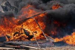 Brännande bilgummihjul, stark flamma av röd brand och moln av svarta dunster royaltyfria bilder