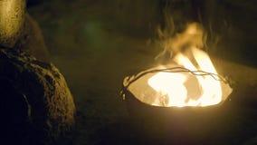 Brännande flammabrand i kastarekruka på den mörka aftonen Turist- brand som bränner i kokkärlkruka i mörk natt, medan campa lager videofilmer