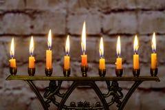 Brännande hanukkah stearinljus i en menora på färgrika stearinljus från en menora Fotografering för Bildbyråer