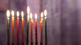 Brännande hanukkah stearinljus i en menora på färgrika stearinljus från en selektiv mjuk fokus för menoror