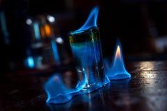 Brännande skottcoctail i stång med låga ljus royaltyfri bild