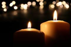 Brännande stearinljus över svart bakgrund med bokeh blänker ljus Arkivfoton
