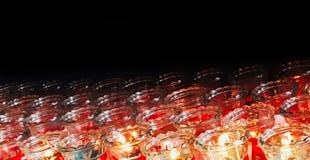 Brännande stearinljus i exponeringsglas för böner i tempel arkivbilder