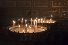 Brännande stearinljus i katolsk kyrka Royaltyfri Bild