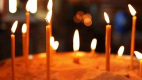 Brännande stearinljus i sanden i Christian Orthodox Church stock video