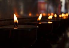 Brännande stearinljus i thailändsk tempel arkivbild