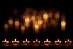 Brännande stearinljus med festlig guld- bokeh royaltyfri foto