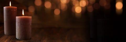 Brännande stearinljus med festlig guld- bokeh arkivfoton
