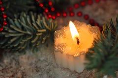 Brännande stearinljus med julgarneringar Arkivbild