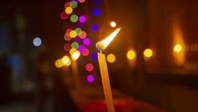 Brännande stearinljus med svaga kulöra ljus i bakgrund royaltyfri fotografi