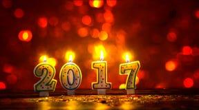 Brännande stearinljus numrerar 2017 och färgrika stänk med bokeh in Royaltyfria Foton