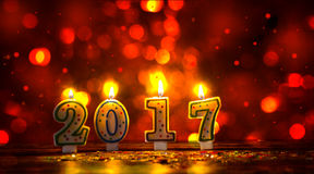 Brännande stearinljus numrerar 2017 och färgrika stänk med glitteri Royaltyfria Bilder