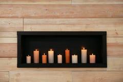 Brännande stearinljus på hylla arkivbild
