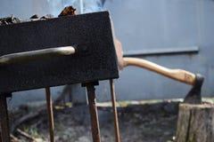 Brännande vedträ i den gamla fyrpannan med en yxa i stubben i bakgrunden royaltyfri fotografi