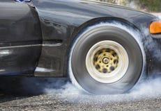 Bränner den tävlings- bilen för friktion gummi av dess gummihjul Arkivfoton