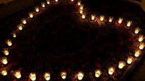 Brännhet hjärta Ordnade stearinljus i en hjärtaform Animering av bakgrund med glödande stearinljus i en hjärtaform för film arkivfilmer