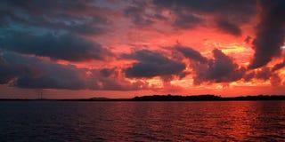 Brännhet molnig solnedgång över vatten Royaltyfria Foton