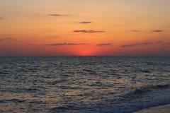 Brännhet röd solnedgång över havet arkivbild