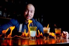 Brännhet show på stången Bartendern gör den varma alkoholiserade coctailen och antänder stången Bartendern förbereder en brännhet royaltyfri foto