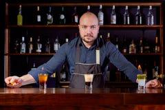 Brännhet show på stången Bartendern gör den varma alkoholiserade coctailen och antänder stången Bartendern förbereder en brännhet arkivfoton