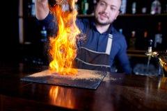 Brännhet show på stången Bartendern gör den varma alkoholiserade coctailen och antänder stången Bartendern förbereder en brännhet arkivbilder