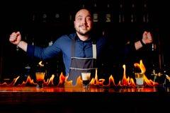 Brännhet show på stången Bartendern gör den varma alkoholiserade coctailen och antänder stången Bartendern förbereder en brännhet royaltyfri fotografi