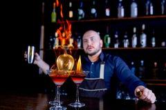 Brännhet show på stången Bartendern gör den varma alkoholiserade coctailen och antänder stången Bartendern förbereder en brännhet royaltyfria foton
