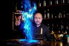 Brännhet show på stången Bartendern gör den varma alkoholiserade coctailen och antänder stången Bartendern förbereder en brännhet royaltyfria bilder