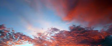 Brännheta moln i den blåa himlen under en solnedgång Royaltyfri Bild