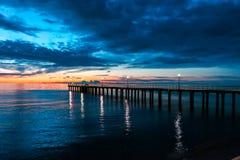 Brännhett moln och himmel över havet på solnedgången med en pir arkivfoto