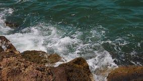 Bränning med havsvågor och för skum stenar nära på kusten, ultrarapid arkivfilmer