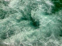 Bränning med virvlande runt vatten som bakgrund royaltyfria bilder