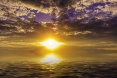 Bränning sol som stiger ned in i djupen av havet Arkivfoton