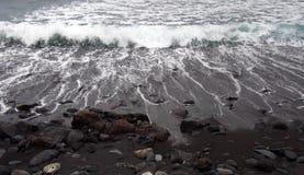 Bränning som bryter på en svart sandstrand med kulöra kiselstenar och stenar i puerto de la cruz tenerife royaltyfri foto