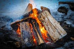 Bränningen loggar in en snöig vinter med rök arkivbilder