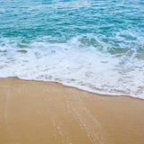 Bränningvågen täcker en havsstrandsand royaltyfria foton