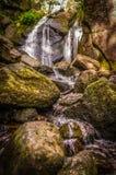 Brännskada O& x27; Vat i Muir av den Dinnet vattenfallet i Skottland med lång slutarehastighet Arkivfoton