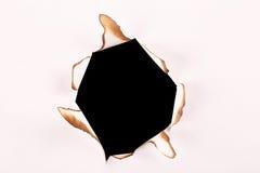 Bränt hål i papper mot en vit bakgrund Arkivbilder