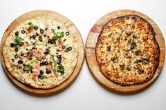 Bränt och det normala Två pizza med tomater, lax, champinjon, peperoni på bästa sikt för trälantlig bakgrund Royaltyfri Fotografi