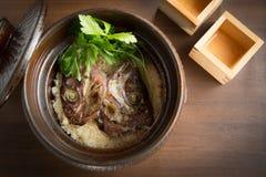 Bräserat fiskhuvud med ris i kruka på tabellen Royaltyfria Bilder